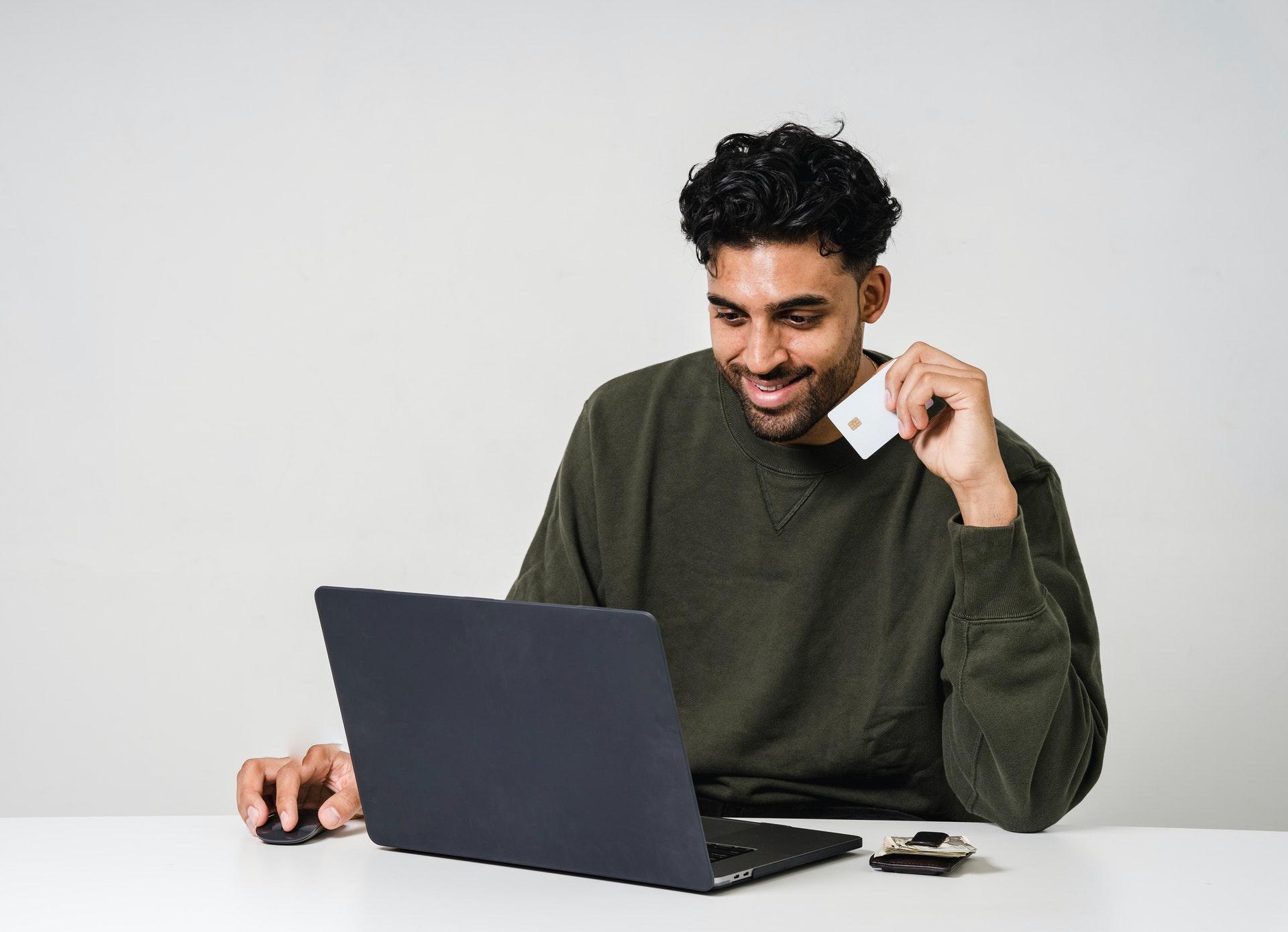 jeune homme pull vert tenant carte de crédit achat en ligne sur ordinateur